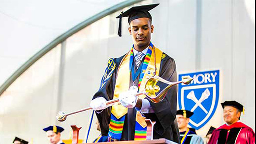 A student in graduation regalia speaks at a podium at a previous Emory Commencement