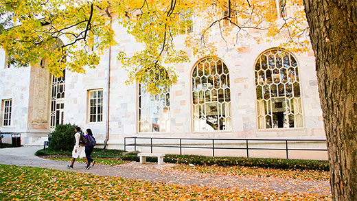 A fall photo of two students walking in front of Emory's Convocation Hall