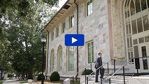 President Fenves walks up a set of stairs into Convocation Hall
