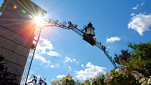 A view of the top of the arch of the Emory gates, with the blue sky and glaring sun above.
