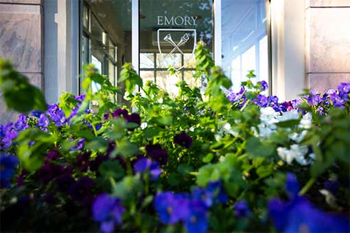 flowers in front of a window with the Emory logo
