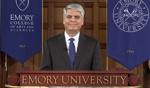 President Fenves speaks from a podium flanked by Emory gonfalons.